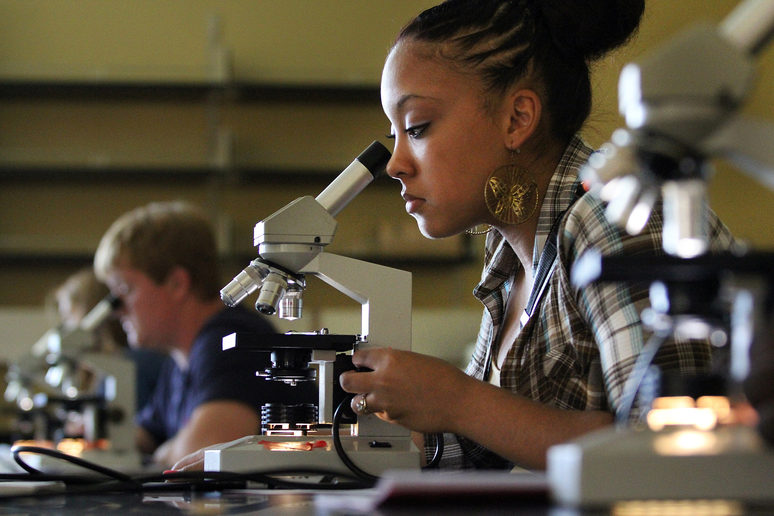 Students using microscopes in a lab setting
